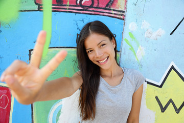 Urban young girl showing v peace sign in city