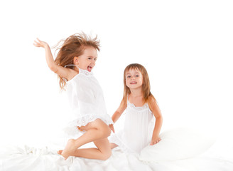 happy family .  kids twin sisters jumping on the bed, playing an
