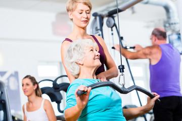 Seniorin beim Rückentraining mit Trainer im Fitness Sport