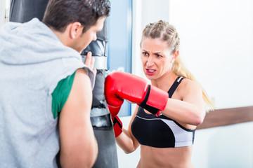 Junge Frau mit Trainer beim Boxen