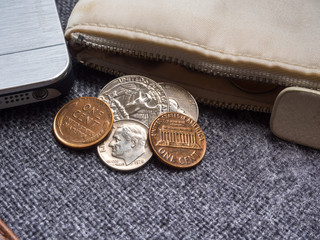 US dollar coins placed outside the wallet with smartphone.