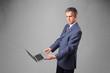 Handsome businessman holding modern laptop