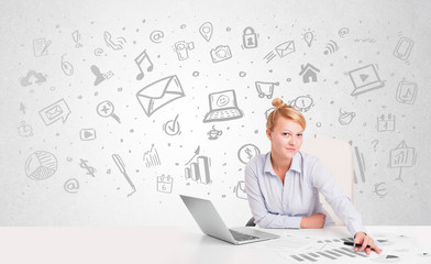 Business woman sitting at table with hand drawn media icons