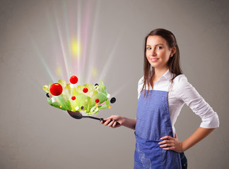 Young woman cooking fresh vegetables
