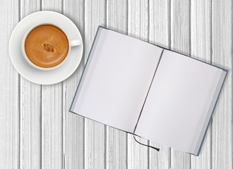 White cup of coffee and opened blank notebook on wooden backgrou