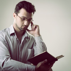 Young handsome thoughtful business man reading book, toned