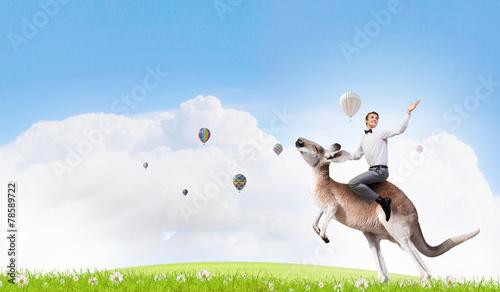 Foto op Canvas Kangoeroe Man saddling kangaroo