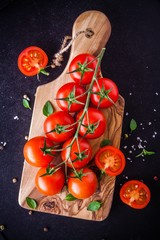 a bunch of organic cherry tomatoes in olive cutting board