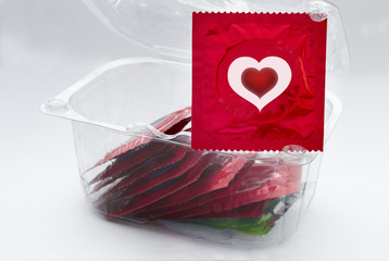 Red condom with heart and a transparent box with a lot of condom