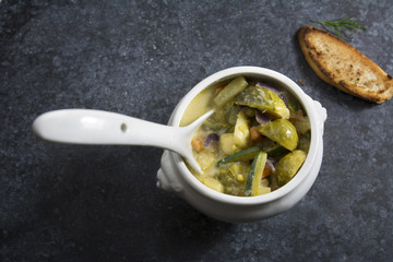 Vegetable soup in white bowl on a dark background with texture