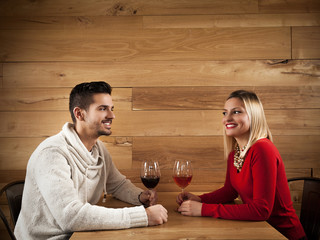 Young couple sitting in a bar drinking wine and talking