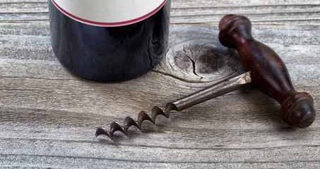 Aged corkscrew and wine bottle on rustic wood