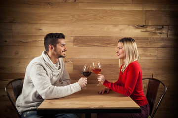Young couple toasting with wine in a restaurant