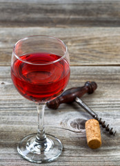Glass of red wine with corkscrew and cork on aged wood