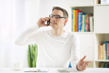 Young businessman working at home using mobile phone