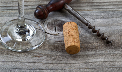 Used cork with corkscrew and wine glass in background on aged wo