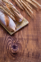 ears of wheat and baguettes on vintage board with copyspace