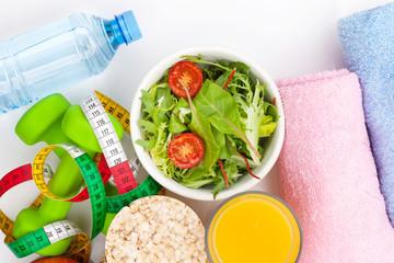 Dumbells, tape measure, healthy food and towels