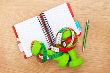 Dumbells, tape measure and notepad for copy space. Fitness and h