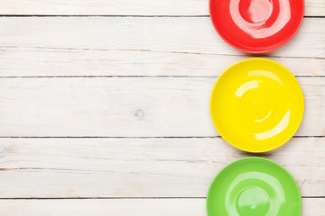 Colorful plates over white wooden table background