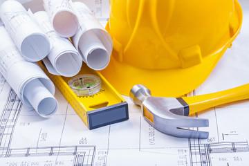 rolls of white blueprints helmet level claw hammer construction