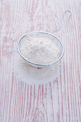 white natural flour  in sieve on vintage wooden desk food and dr