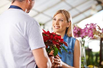 Kunde kauft Weihnachtsstern in Blumenladen