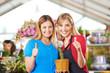 Frauen im Gartencenter halten Daumen hoch