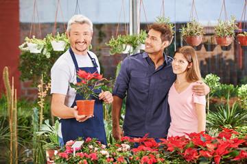 Paar neben Gärtner mit Weihnachtsstern