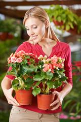 Frau hält Begonien im Gartencenter