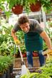 Gärtner gießt Pflanzen mit Wasser