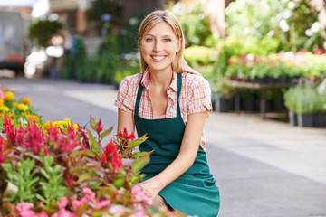 Frau als Gärtner vor Blumenladen