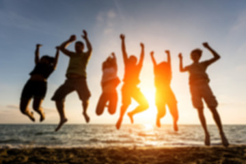 Group of people jumping at beach, blurred background.