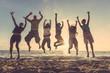 Leinwanddruck Bild - Multiracial group of people jumping at beach