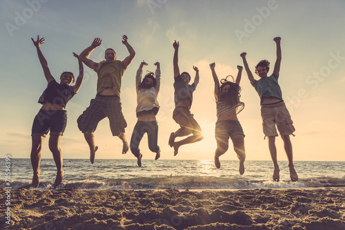 Leinwanddruck Bild Multiracial group of people jumping at beach