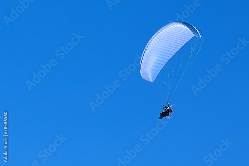 Leinwandbild Motiv powered paragliding in the blue sky