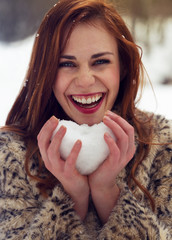 Beautiful woman holding snow heart
