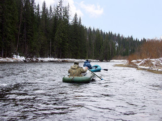 Two men floated on the spring mountain river on inflatable boats