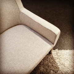 Beige textile armchair on a carpet