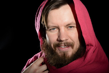 portrait of a bearded man in a studio in a red cape