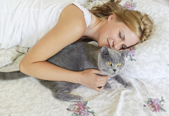 Young beautiful woman with british cat on the bed