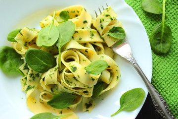 Tagliatelle pasta with spinach sauce on a white plate