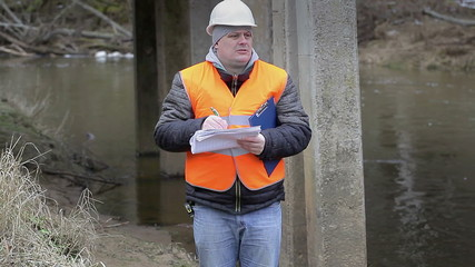 Engineer writing the documentation under the bridge