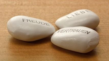 Drei Steine beschriftet mit den Worten Freude, Liebe, Vertrauen.
