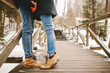 Hipster couple kissing on wooden stairs in winter park