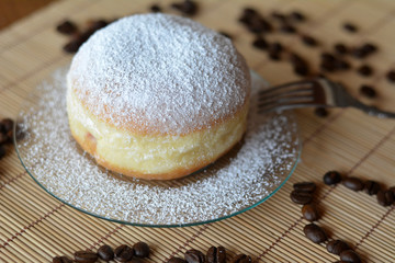 Delicious donut with icing sugar on plate on the table