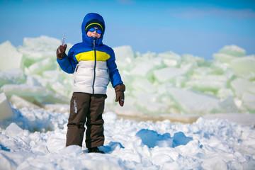 Cute little boy outdoors standing on winter beach