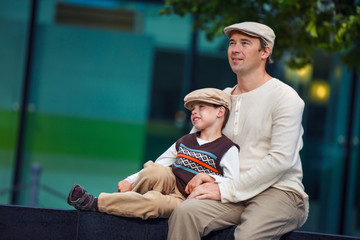 Happy father and son having rest outdoors in city
