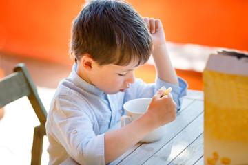 Cute little boy eating dairy breakfast