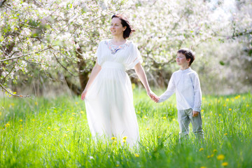 Happy woman and child in blooming garden